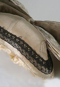 Tykkimyssy, koppa ja tykkipitsi  | Kuvaus: kapea, munuaisen muotoinen pahvikupu on päällystetty vaaleanvihreällä silkkisatiinilla ja vuoritettu vaaleanpuna-valkoruudullisella puuvillapalttinalla. Takana suuri silkkinauharusetti. | Lahden kaupunginmuseo/Lahden historiallinen museo, esinenumero LKM/LHM/LHM/ES/2009002/71