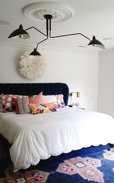 Ceiling medallion paired with modern black chandelier. Elevate your bedroom decor. Eclectic modern.