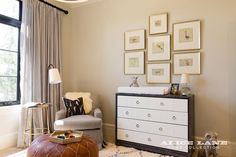 Gray and gold nursery features a gray glider lined with a black pillow as well as a brown leather Moroccan pouf placed next to a gold stool table illuminated by a an iron drum floor lamp.