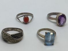 LOT OF FOUR STERLING SILVER RINGS, WITH STONES. INCLUDES AMETHYST (SIZE 9.5), CARNELIAN (10), CRYSTALS AND MARCASITE (9.5) AND A 14K GOLD ELECTROPLATED RING WITH A BLUE STONE (7.5).