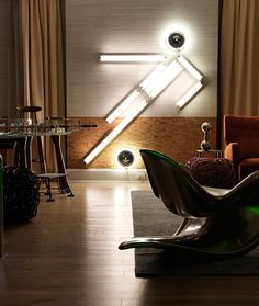 """Gallet's goal was to create an atmosphere where adults could escape and revert back to their inner child. The light sculpture on the wall, """"Nowhere Man 7"""" by Ivan Navarro, sticks to the sports theme while also giving a youthful vibe to the room. www.traditionalhome.com"""