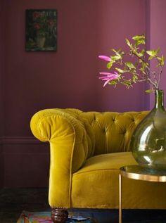 peinture aubergine, table basse ronde, sofa moutarde capitonné, vase avec des fleurs,