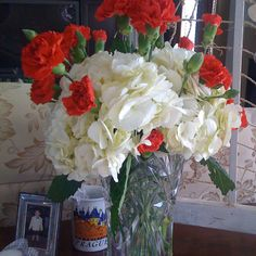 White hydrangeas with red carnations.