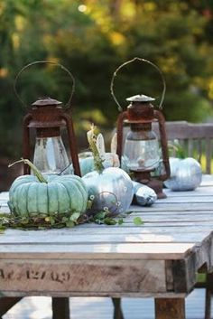 pumpkins, lanterns on a wooden outdoor table.
