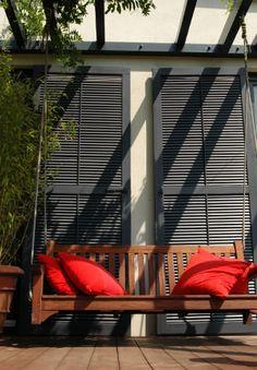Schicke Landhaus Terrassengestaltung mit Pergola, daran befestigter Schaukel und dunkelbraunen WPC Dielen