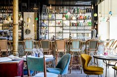 stunning cafe in Barcelona, Spain- chairs covered in velvet, black and mirrored walls, woven French bistro bar stools and a plethora of pendants. Love the various barstool colors.
