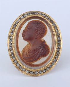 Finely carved Neo-classical hardstone cameo of a blackamoor, circa 1790 - 1800, set to a high-carat gold and rose-cut diamond mount, circa 1820.