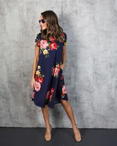Our Rosemary Floral Dress is perfect for your work or weekend festivities! It's navy base is complemented by red and pink rosettes throughout. The high neck and short sleeves are too cute on this swin