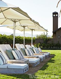 """Umbrellas from Janus etCie provide shade tothe chaise lounges from Sutherland's """"Poolside"""" Collection."""