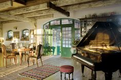 Living/dining room with rough hewn beams and green French doors -- farmhouse in Poland