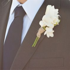 The boutonnieres will be white freesia with green leaves wrapped in plum ribbon.