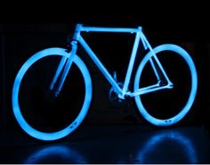 Glow in the dark bicycle helps with cycling safely. Get #climate-smart and cycle instead of driving. Neon blue bike on black background