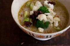 Ten Minute Couscous Soup - a pot of quick-cooking, beautiful, brothy couscous soup topped with a bit of melted goat cheese and bright broccoli and cauliflower florets. It is all punctuated with a spoonful of finely chopped sun-dried tomatoes. - from 101Cookbooks.com