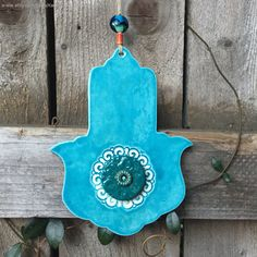 This beautiful one-of-a-kind Hamsa was formed using high-fire white earthenware clay, in hand-built method. Using my various stamps and tools, I cut and textured this beautiful hamsa shape, then fired it to bisque. After taking it out of the kiln, I glazed it with lead-free teal blue glaze and high fired it again in my kiln at my studio. Ceramic hamsas by KerenOrHandmade on Etsy