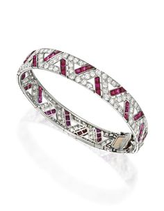 PLATINUM, DIAMOND AND RUBY BRACELET, CIRCA 1925. Of geometric design, set with numerous old European and single-cut diamonds weighing approximately 7.00 carats, accented by numerous calibré-cut rubies, internal circumference 7 inches.