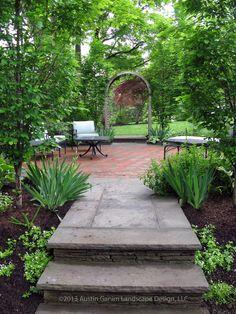 European hornbeam frame the circular brick and bluestone patio of the shade garden, Southport, CT.