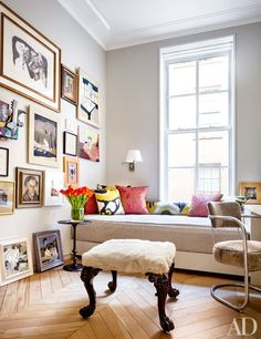 The guest room, painted in a Benjamin Moore gray, features a wall of artworks, including several by Lucien Rees Roberts | archdigest.com