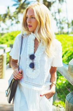 Shea Marie wears a white dress with ruffle detailing, a gray Chloe bag, and clear frame sunglasses