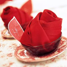 "Make napkin ""roses"" by folding a napkin lengthwise in several folds, then rolling it up to form a rosebud. Set these in little bowls and garnish with a place card cut in a leaf shape."