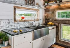 """The luxurious Alpha Tiny Home, which was recently showcased on HGTV's """"Tiny House, Big Living,"""" boasts trend-forward details like reclaimed barn wood, subway tiles, hardwood floors, and a stainless steel farmhouse sink."""