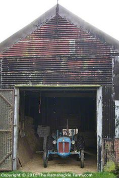 Front of old English threshing barn now clad with corrugated metal sheeting sheltering Fordson Dexta tractor.  East Anglia, UK.