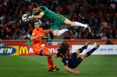 Iker Casillas of Spain catches the ball ahead of Robin Van Persie of the Netherlands as Carles Puyol of Spain falls to the ground during the 2010 FIFA World Cup South Africa Final match between Netherlands and Spain at Soccer City Stadium on July 2010 Soccer City, Football Soccer, Soccer Pro, Van Persie, Fc Porto, World Of Sports, Sports Photos, Fifa World Cup, Goalkeeper