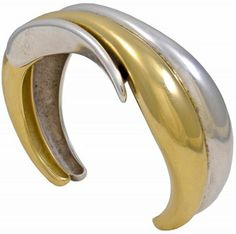 Georg Jensen 'Minas' Gold and Sterling Bracelet No. 405. This cuff bracelet No. 405 was designed by Minas Spiridus for Georg Jensen is in 18 karat gold and sterling silver. This bracelet is circa 1990's. The bracelet measures 2.25 by 1.5 inches (internally) and measures 3/4 inch wide across the top. The bracelet weighs approximately 73.6 grams and is in excellent condition.