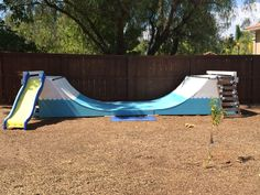 Our backyard half pipe with a little rock wall climb up, slide, and blue wave paint pattern. #Backyard #Playscape #Skateboarding #Halfpipe
