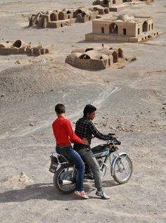 MAX NEUFEIND: Zwei junge Männer fahren mit ihrem Motorrad durch eine zoroastrische Kultstätte in Yazd. Der Zoroastrismus ist eine der ältesten Religionen des Landes. Heute leben noch etwa 25.000 Zoroastrier im Iran.