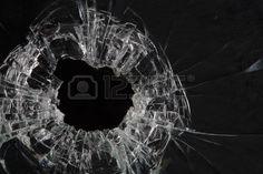 agujeros de bala en el vidrio aislado en negro Foto de archivo