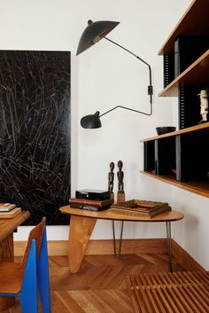 Home of art collector and gallerist couple Miquel Alzueta and África Posse in Barcelona, Spain: Standard chair by Jean Prouvé (1934/1950), Nuage bookshelf by Charlotte Perriand (c.1958), Rudder dinette table by Isamu Noguchi (c.1949) and a large wall light by Serge Mouille (c.1950s). Photography by Jonas Ingerstedt for Kinfolk. / Ingerstedt