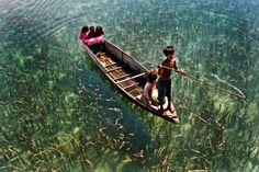 Crianças passeiam em um barco em um lago de águas cristalinas em Sabah, Malásia.