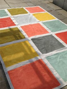 This weekend's DIY: A rug made from a 6x9 canvas drop cloth, painters tape and seven different colors of paint (all in those little tester sizes from Home Depot) from our Canyon Sunrise palette. The...