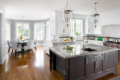 There are so many things I love about this kitchen including bright white cabinets beautifully contrasted with the dark island, pendant lighting, marble backsplash tile, elegant dining table and chairs, large windows letting in light, etc