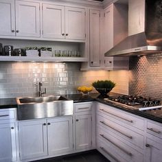 stainless farmhouse sink, combo of subway tile on one wall and glass mosiac above the cooktop, stainless vent hood that is vented to outside