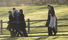 The Duke and Duchess of Cambridge link arms as they follow other members of the Royal Family into church