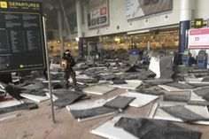 A soldier walks through debris after two explosion rocked a terminal building at Brussels ...