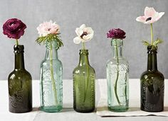 Tinted bottle centerpieces with single flowers. ----- I like the idea of different colours of glass and the texture on the bottles.
