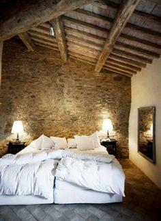 Heerlijke slaapkamer met een stenen vloer en houten dakconstructie. In combinatie met het smetteloos wit dekbedovertrek maakt het een slaapkamer om in weg te dromen.