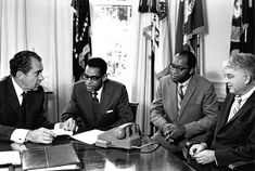 President Nixon sitting at his Oval office desk during a meeting with Equal Employment Opportunities Commission Chairman William H. Brown III, Counselor Arthur F. Burns, and Special Assistant Robert Brown.  August 9, 1969.