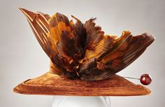 Silk velvet hat with tall crown and wide brim. Large, sculpted feather accent and original hatpin, circa 1914-1918 via eBay