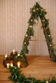 woodland rustic wedding ceremony with tree stumps candles moss arch for bride and groom to stand in front made from ladders