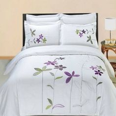 Modern Hotel Style Purple White Embroidered Floral Duvet Comforter Cover and Shams Set with Decorative Pillows. The bedding set is made of luxury 100 percent egyptian cotton for softness. Features embroidered purple and green flowers on a white background.