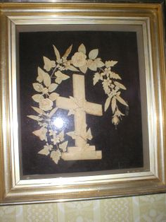 Archive photo: Framed shadow box with wreath of wax flowers with cross - 1890.  In wide gold frame. Circa 1890. Made and donated by Maria L. Luce. As seen on the wall in the music room of the Historic Atwood House, Chatham, MA. #atwoodhouse, #musicroom, #was, #frame, #chathamhistoricalsociety, #chatham, #capecod