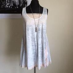 Free people cream lace top Free people cream lace top with light pink all around pink lace - The long cream colored top is used  please note that it has a tiny hole on the back kind of by the right shoulder blade area - 50% cotton- 50% polyester. Free People Tops Tank Tops