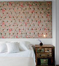 No quarto do casal, o painel de laca estofado ocupa toda a parede, assumindo o papel de uma grande cabeceira. Para iluminar o criado-mudo, pendente, da Lustres Iriê. Roupa de cama de linho, da Casa Almeida