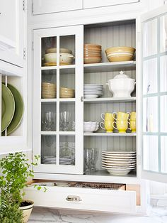 Cottage Kitchen Traditional glass-front cabinets flank the window, making the room look brighter. Beaded board, carried over from the backsplash, lines the cabinet interior. A collection of vintage dishware on display is both pretty and practical.