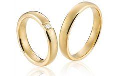 V526 - de kracht van de eenvoud. Prachtige geelgouden trouwringen met in de damesring een briljant die wel lijkt te zweven.