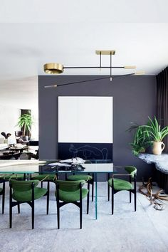 Dinning space with a gray contrast wall, a glass table, green velvet chairs and a modern gold chandelier