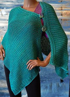 """This shawl/wrap can be worn buttoned down the front or asymmetrically along the shoulder. The buttons are handmade and color matched to the beads. The borders along one edge and at the ends are beaded. The silk merino and rayon metallic compliment each other well. It was an easy knit so I made three. The colors not shown are """"Plum"""" and """"Terra"""". The kit is available from Blue Heron Yarns at:"""